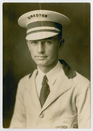 Old photograph of a man in a white jacket and tie. The man is also wearing a hat with the word Director on it. The photograph has a tear on it at the top.