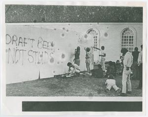 Black and white photograph of a group of people outdoors. Some paint on a large white fence near a building. The words Draft Beer Not Studs is painted on the fence.