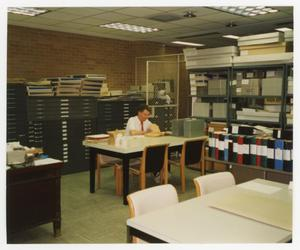 Color photograph of an man sitting at a table in a room filled with map cabinets, and shelves of boxes.