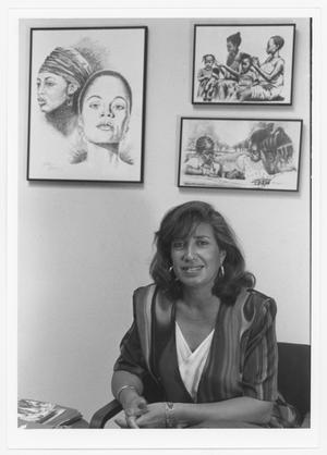 Black and white photo. A woman sits in a chair. Behind her on the wall are three sketches of women and young girls.