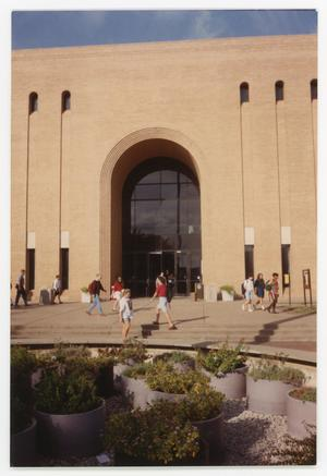 Color photograph of the exterior of the Willis Library building entry, with a fountain in the foreground. The fountain has been drained of water, and has rocks in the bottom with many flower pots inside.