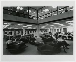 Black and white photograph of the interior of a building. People are seated in an area with various oval seating units, where the ceiling opens up to view the glassed-in floor above. In the background are bookshelves and desks.