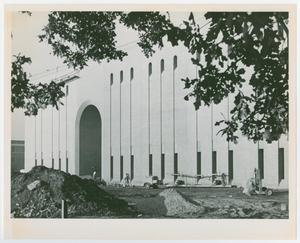 Black and white photo looking diagonally at the front of Willis Library. The facade is a long rectangle with a tall archway towards the left of the building, and a row of narrow windows along the top and bottom of the building.