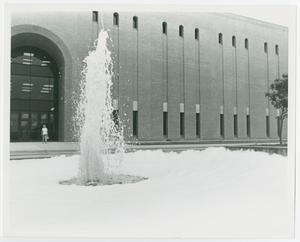 Black and white photograph of a fountain in front of a building. Water shoots up from the center and soap bubbles fill the rest of the fountain.