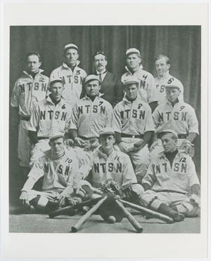 Black and white photo of 11 men in rows of 3. They all wear white jackets with the letters NTSN on them. They also wear white hats. The man in the middle of the back row is wearing a suit instead, and has a moustache.