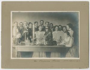 Foto en blanco y negro de un grupo grande de personas reunidas alrededor de una mesa. La fotografía está montada en un tablero gris con bordes blancos.