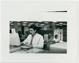 Black and white photograph of a man at a computer. In the background another person is seated at a desk, and card catalog units can be seen in the background.