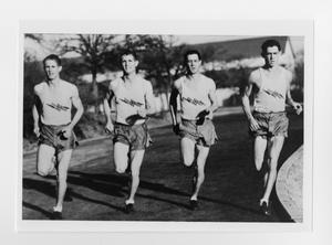Black and white photo of four men in shorts and tank tops running together on a track.