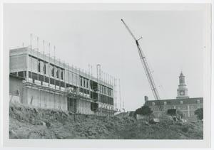 Black and white photo of the front of a building under construction with scaffolding along the buildings facade. A crane and another building with a clocktower can be seen in the background.