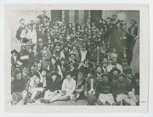 Black and white photo of a big group of people bundle up together.