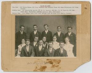 Una fotografía en blanco y negro de 14 personas en 2 filas. Hay 4 mujeres dispersas en la imagen. Arriba de la foto, en el tablero de respaldo, hay una tira de papel blanco con texto.