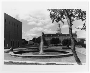 Black and white photograph of fountain on a library mall, the Hurley Administration building is in the background.