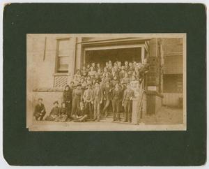 Una fotografía antigua montada sobre papel negro, donde aparecen muchas personas agrupadas en una escalera con una puerta abierta.