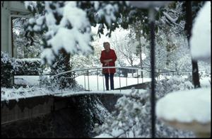 Primary view of object titled '[Lela Sparkman standing on a snow-covered bridge, 1978]'.