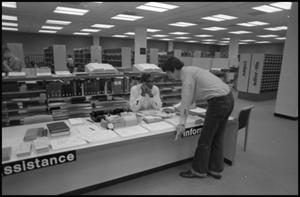 Black and white photograph of a student leaning over a low desk with an information sign. He speaks to a woman sitting behind the desk. There are many book shelves behind the desk.