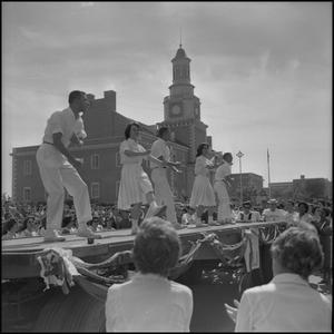 Black and white photograph of three male and two female cheerleaders standing on an elevated stage. The women wear long pleated skirts, and the men wear all white button down shirts and slacks.