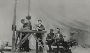 Two men stand by a table, on the right are two men sitting down, one of them holding a small guitar.