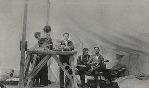 Dos hombres están de pie junto a una mesa, a la derecha hay dos hombres sentados, uno de ellos sosteniendo una pequeña guitarra.