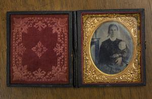 A small open book. The left side of it is red with an intricate design. The right side of it is a black and white photo of a woman holding a baby.