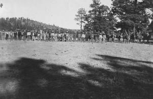 Foto en blanco y negro de una multitud de personas de pie en el fondo, están en un campo abierto.