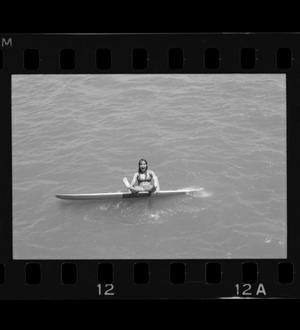 Primary view of object titled '[A girl sits on a surfboard]'.