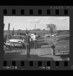 Primary view of object titled '[Jim and Roger walking through a junkyard]'.