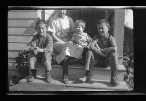 Primary view of object titled '[Photo of Irene Williams sitting on a porch with her sons]'.