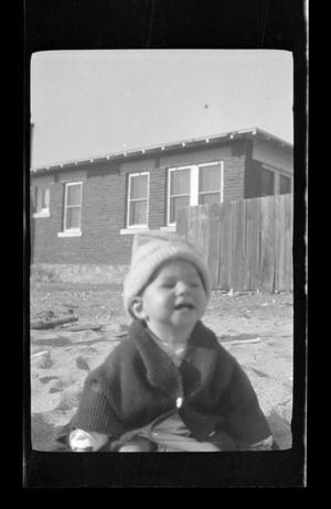 Primary view of object titled '[Charles Williams sitting in front of a house]'.