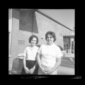 Primary view of object titled '[Two women sitting on a car in front of a barber shop]'.