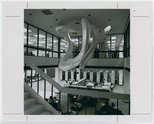 Black and white photograph from a staircase, of a large abstract sculture hanging from a ceiling. The first floor is visible below, with desks and bookshelves, and the second floor is visible through a wall of windows surround the sculpture.