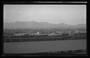 Primary view of object titled '[Photo of trains with a city in the distance]'.