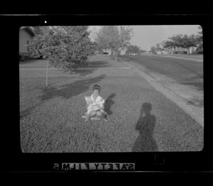 Primary view of object titled '[A girl sitting in the front yard]'.