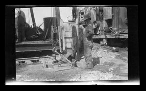 Primary view of object titled '[Photo of a man mixing cement]'.