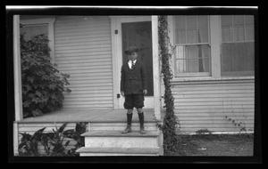 Primary view of object titled '[Byrd Williams, III standing on a porch.'.