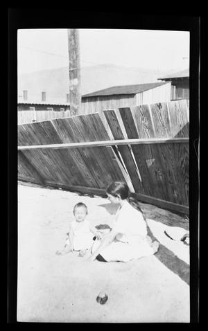 Primary view of object titled '[A girl and a baby sit near a fence]'.