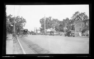 Primary view of object titled '[A street lined with houses and Model T's]'.