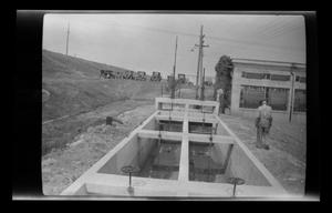 Primary view of object titled '[An old man stands next to a sewage container]'.