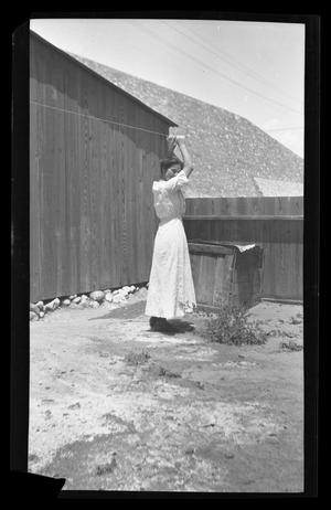Primary view of object titled '[Irene Biffle Williams hanging clothes in the back yard]'.