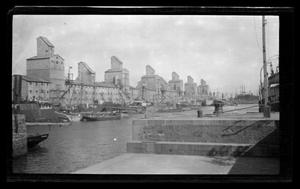 Primary view of object titled '[Unidentified buildings alongside a river]'.