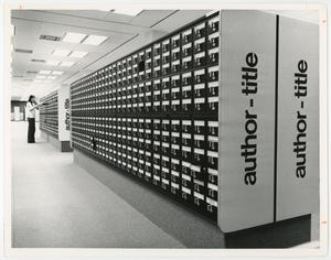 Black and white photograph, at an angle, of two long card catalog units, with black drawer fronts, and light colored ends with the words author-title in black. A man opens a drawed at the far unit.
