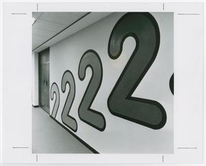 Black and white photograph of a wall with 4 large numeral 2's painted on it. From left to right each 2 is slightly higher on the wall and a slightly darker color.