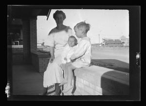 Primary view of object titled '[Photo of Irene Williams and her sons sitting on a porch]'.