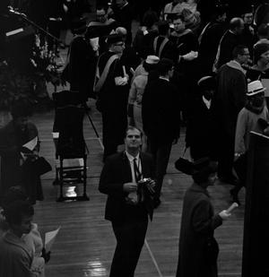 Primary view of object titled '[Man with Camera in a crowd after a Commencement Ceremony]'.