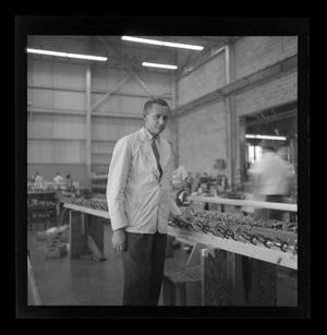 Primary view of object titled '[A Bell employee standing at a work table]'.