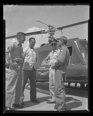 Primary view of object titled '[Crew of YH-40 stopping over at Hurst heliport]'.