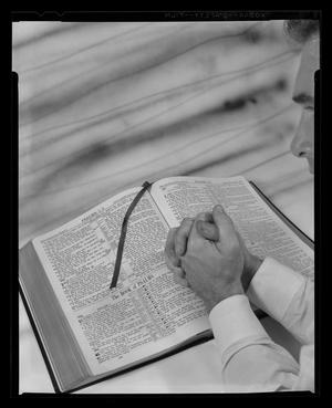 Primary view of object titled '[Man with hands on an open Bible]'.