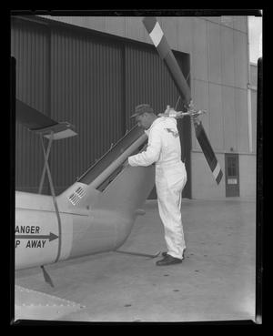 Primary view of object titled '[A Bell employee inspecting the tail of a YH-40]'.