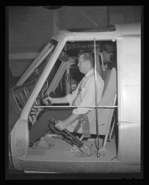 Primary view of object titled '[Bell employee grasping controls of H-40 helicopter]'.