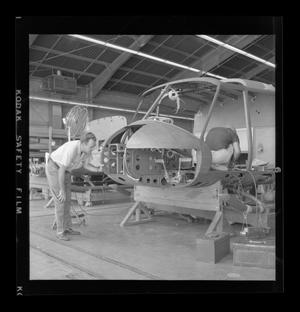 Primary view of object titled '[Bell employees working on the fuselage of an XH-40]'.