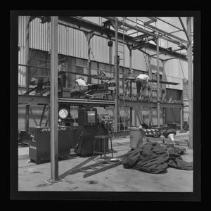 Primary view of object titled '[Bell employees working on the XH-40 blade on the assembly line]'.